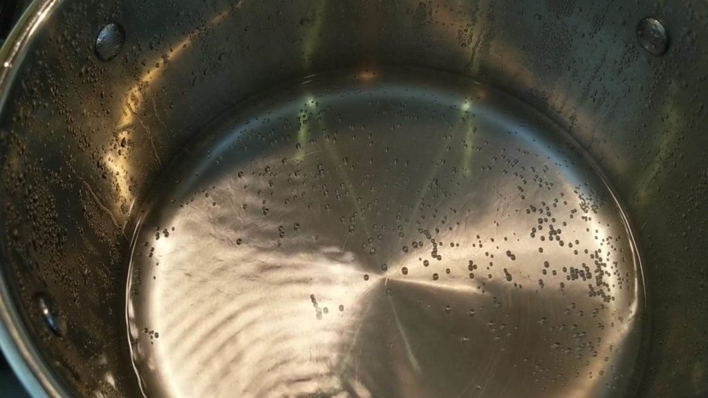 Close up view of water boiling but not enough to start cooking eggs - boil egg